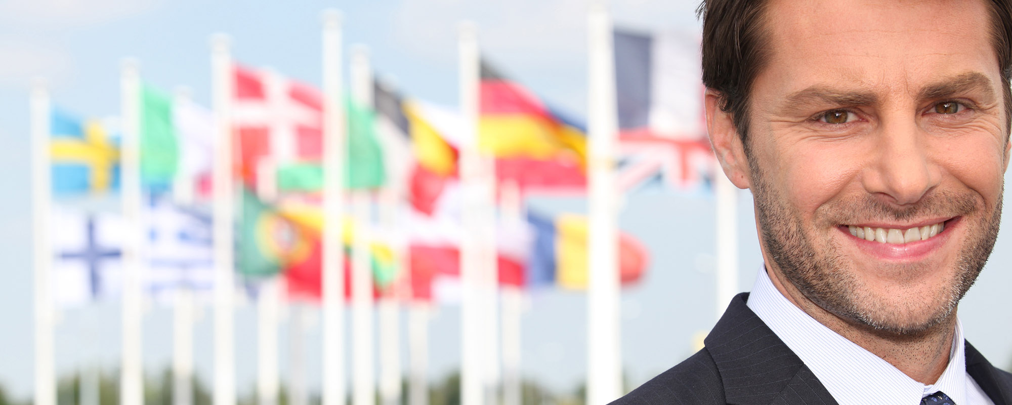 Man in business attire in front of international flags