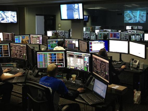 Photo of people working in control room with multiple computer screens